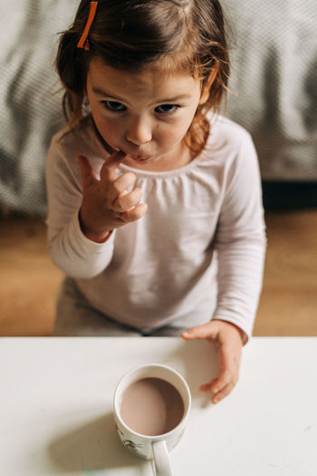 High angle portrait of cute girl standing by hot chocolate at home