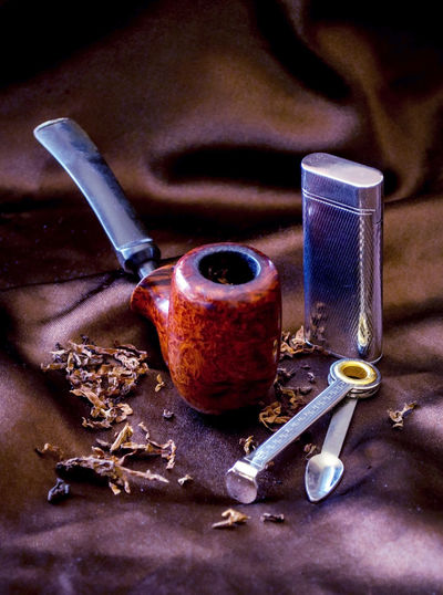 a beautiful wood pipe on black silk with a silver lighter, tobacco and a pipe tool Loose Tobacco Still Life Antique Classic Retro Smoking Addiction Brown Silk Collection Habit Indoors  Lifestyles Lighter Nicotine Pipe Pipe Cleaning Tool Pipe Collector Smoker Smoking Pipe Still Life Tobacco Product Tools Vintage Wood - Material