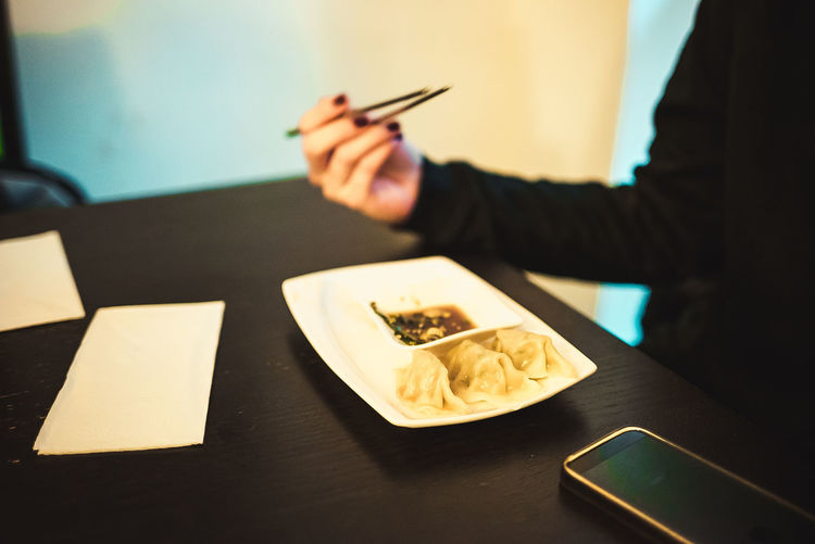 Midsection of woman holding chopsticks while having food at restaurant
