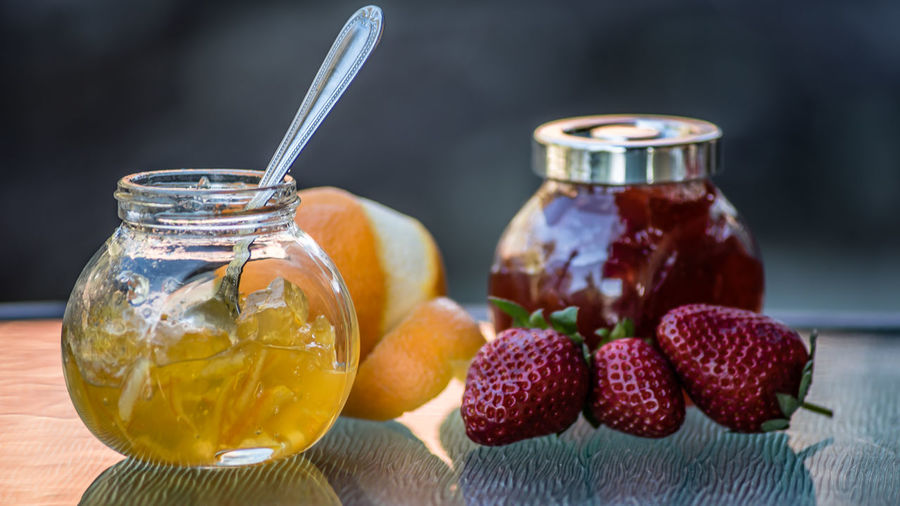 Colorful jams in glass jars and organic fresh fruit, closeup, macro food. Side view of yellow orange marmalade, fresh orange, red strawberry jam and fresh strawberries, side view, selective focus. Orange Red Close-up Focus On Foreground Food Food Photography Food Stories Fresh Freshness Fruit Glass Jars Glass Table Top Jam Jar Macro Marmalade No People Organic Selective Focus Side View Strawberry Table Yellow