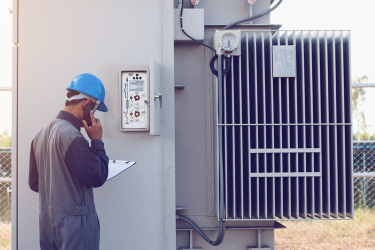 Male engineer talking on mobile phone while checking meter
