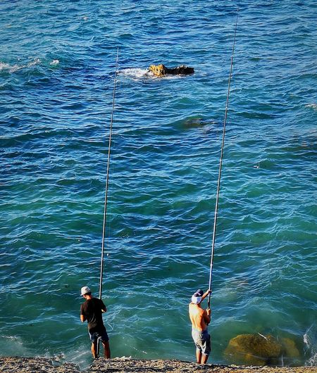 Men fishing in sea