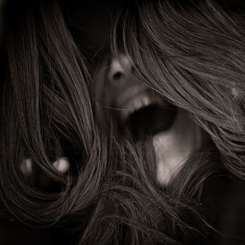 Close-up of young woman screaming in darkroom