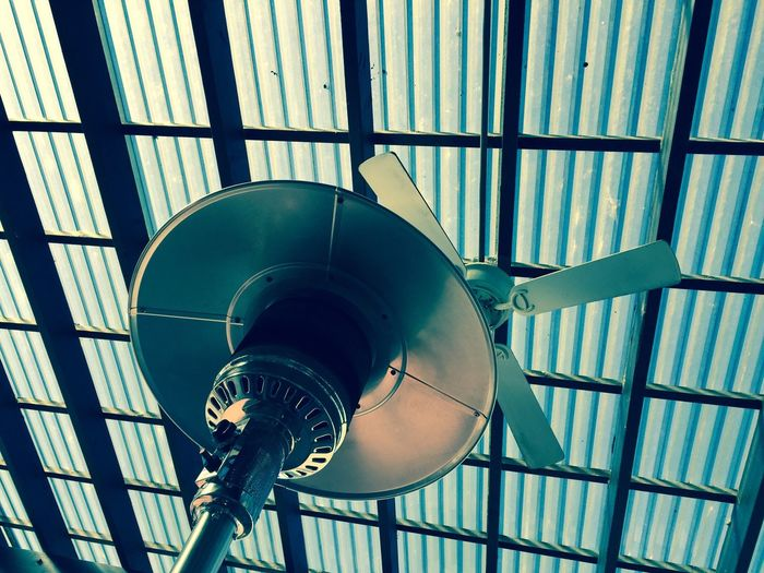 Low angle view of lamp against electric fan hanging from ceiling