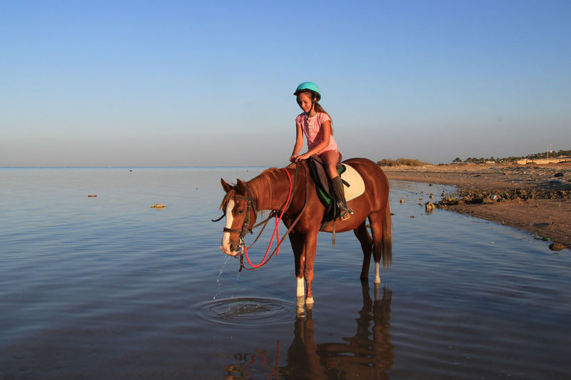 Girl riding horse in sea against blue sky