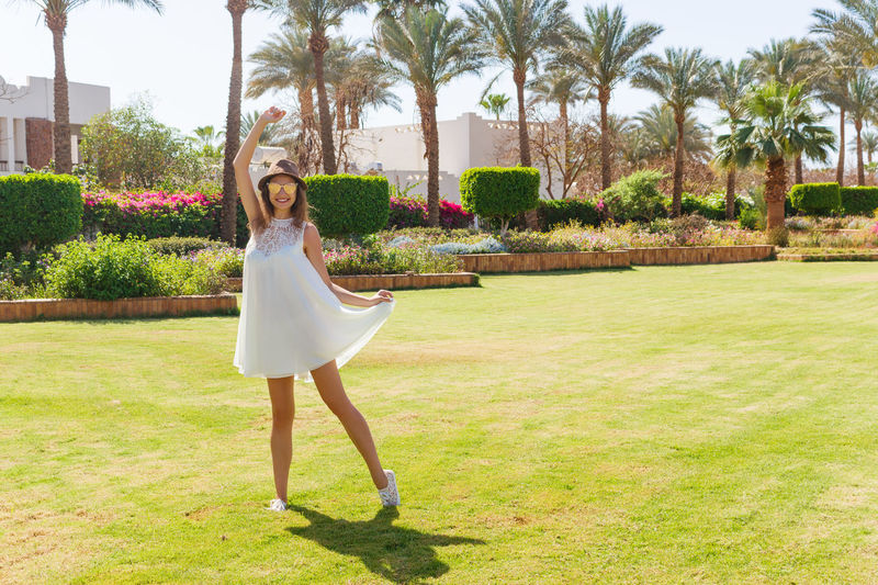 Fashionable young woman wearing white dress while standing in park