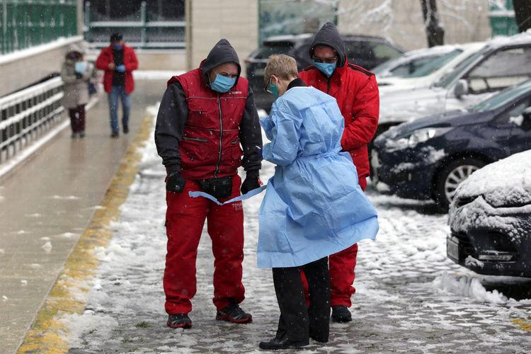 People walking on wet road in winter