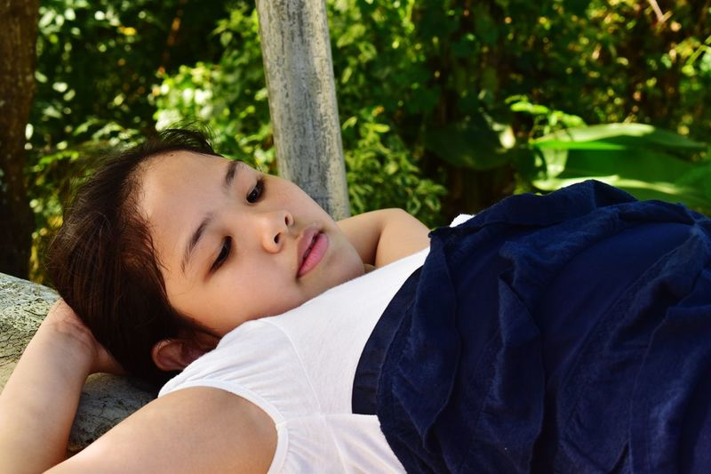 Close-up of young woman lying down against trees