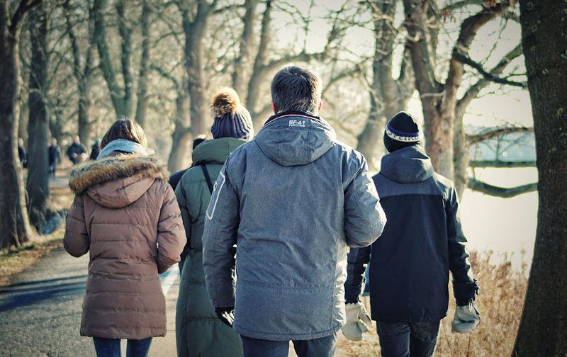 Rear view of people walking in winter