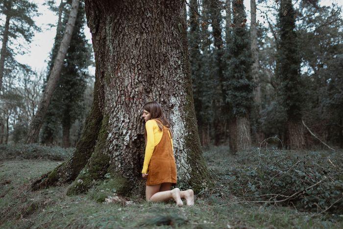 WOMAN STANDING BY TREE ON FIELD