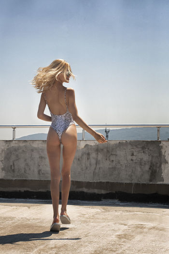 Rear view of seductive young woman walking on building terrace against sky during sunny day