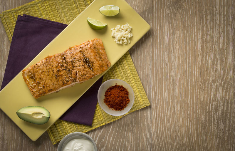 Salmon filet with ingredients Food Table Still Life Ready-to-eat Healthy Eating Wood - Material No People High Angle View Napkin Place Mat Salmon - Seafood Filet Garlic Ingredients Lime Avocado Sour Cream Looking Down From Above Nobody Horizontal Arrangement Chili Powder