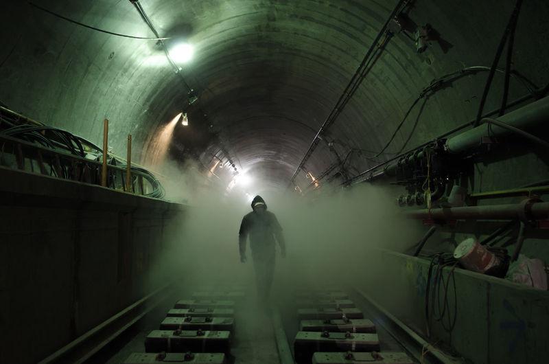 Man Walking Amidst Smoke On Railroad Track In Illuminated Subway Tunnel
