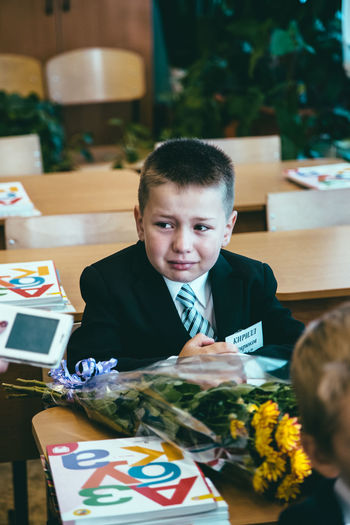 First day in school Boys Child Childhood Front View Headshot Indoors  Innocence Leisure Activity Lifestyles Looking At Camera Males  Men One Person Portrait Real People Sitting Table