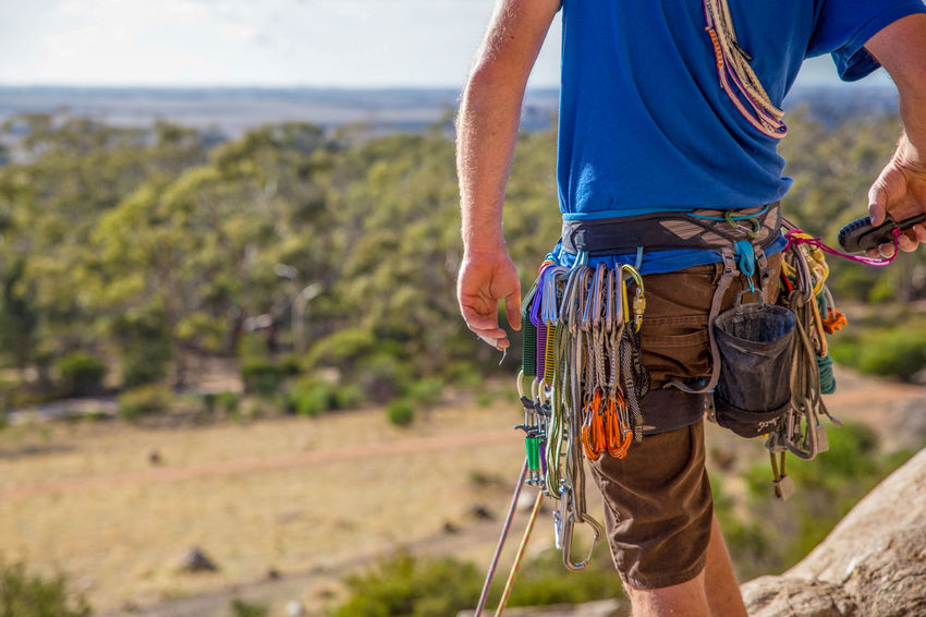 A rock climber checks his gear and radio before climbing Australia Activity Adult Adventure Carabiners Checking Radio Climbing Equipment Day Extreme Sports Focus On Foreground Land Leisure Activity Men Midsection Nature One Person Outdoors Protection Rock - Object Rock Climbing Rope Safety Safety Harness Sport Standing