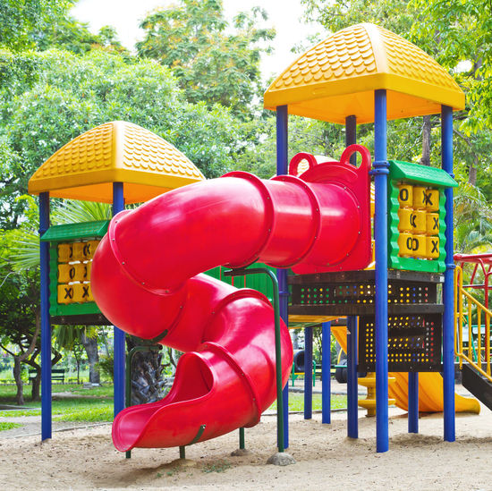Empty playground against trees in park