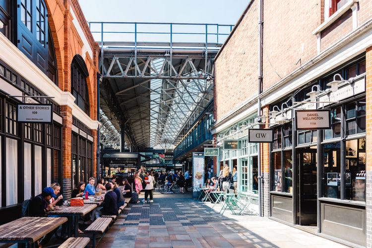 Entrance to Old Spitalfields market with unidentified people. The market hosts arts and craft and street food market. Brexit Britain London Uk Antique Architecture Beautiful British Building Business City Culture Destination England English Entrance Europe European  Flea Food Foodie Gastro Handcrafted Interior KINGDOM Landmark Market Marketplace Merchandise Old People Retail  Retro Revival Shop Shopping Shoreditch Spitalfields Stall Store Street Street Food Tourism Tourist Town Travel Vintage Whitechapel