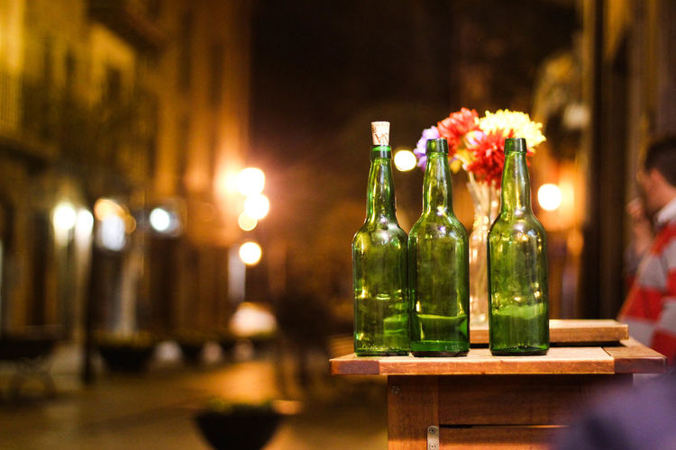 Wine bottles on table by street during night