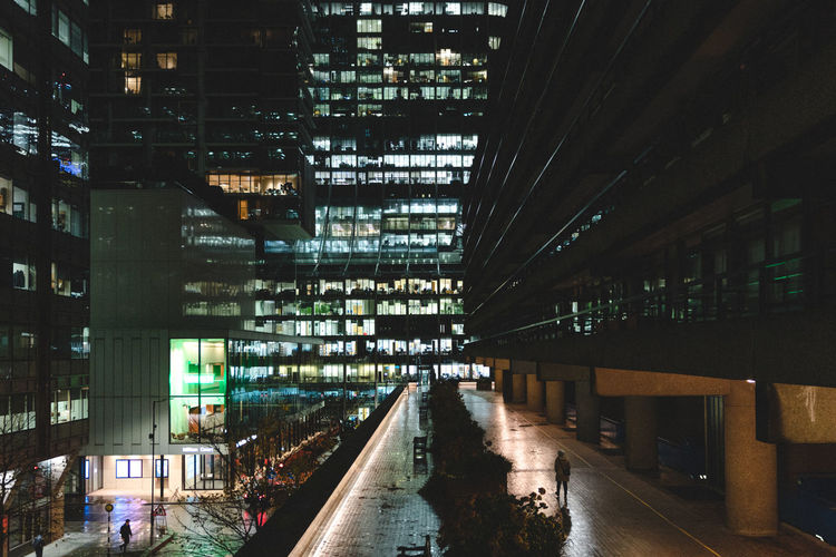 Illuminated bridge amidst buildings in city at night