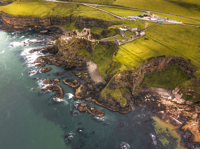 From the see everything looks different Castle Causeway Coast Drone  Dunluce Castle Aerial View Architecture Beauty In Nature Built Structure Coast Dronephotography Environment Green Color High Angle View Land Landscape Nature No People Outdoors Scenics - Nature Sea Tranquil Scene Tranquility Water
