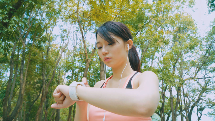 Young Woman Wearing Sports Clothing Exercising In Park