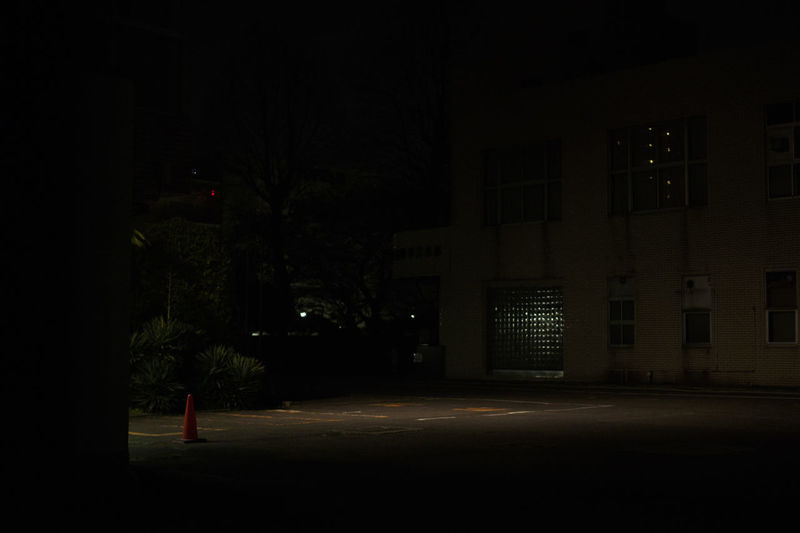Empty road by illuminated buildings at night