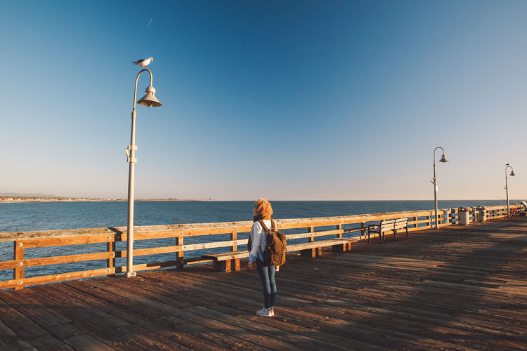 Full length of mid adult woman standing on pier over sea during sunset