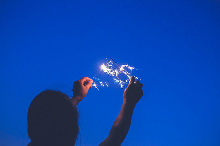 Rear view of woman holding sparklers against clear sky at night