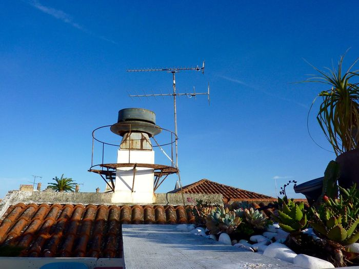 Low Angle View Of Television Aerial On Roof Against Blue Sky
