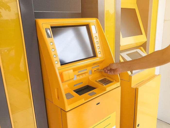 Man's hand is inserting an ATM card in a bank cash machine. Yellow Machinery One Person Human Hand Finance Hand Technology Human Body Part Real People Convenience Indoors  Close-up Lifestyles Credit Card Leisure Activity Entrance Women Accessibility Inserting Atm Banking Cash Withdraw Accounting Business