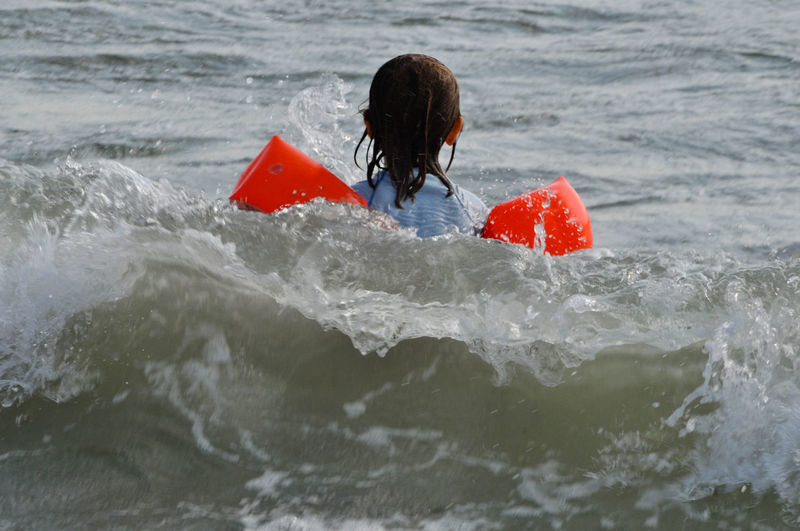 Rear View Of Girl Swimming In Sea