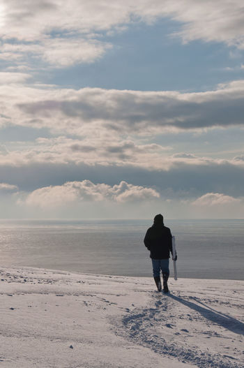 Rear view of man standing on snow covered land by sea