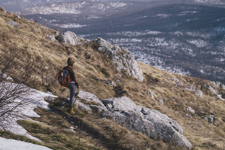 Side view of backpack hiker standing on mountain against landscape during winter