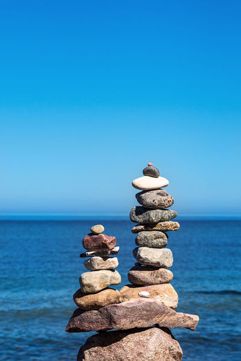 Stack of stones by sea against blue sky