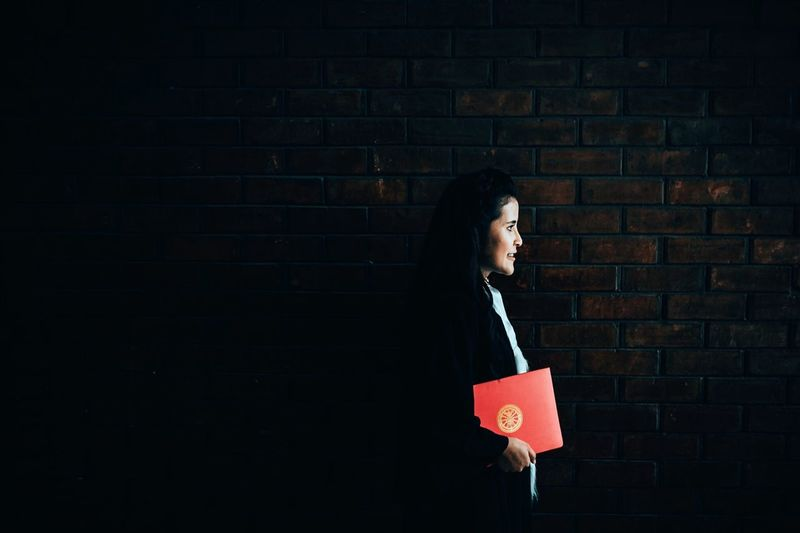 Side view of woman holding book while standing against brick wall