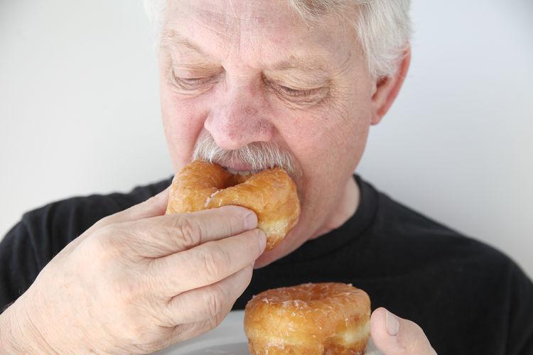 Breakfast Closeup Doughnuts Eating Front View Holding Indulgence Junk Food Man Older Person Senior Snacks Sugary Sweet Food Tasty Treats Unhealthy Eating