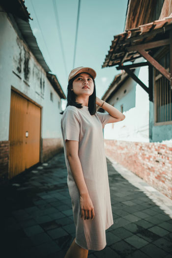 Portrait of young woman looking away while standing outdoors