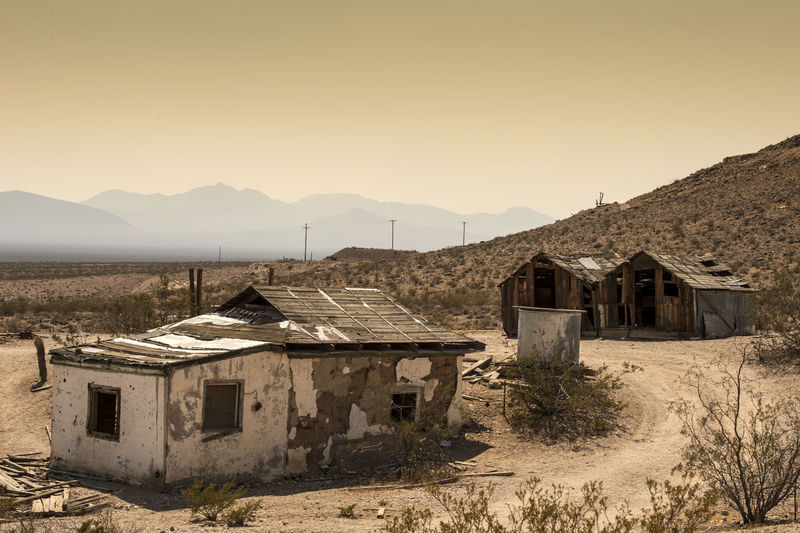 Abandoned houses in ghost town against clear sky during sunset