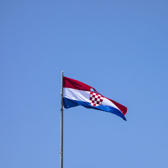 Low angle view of croatian flag against clear blue sky