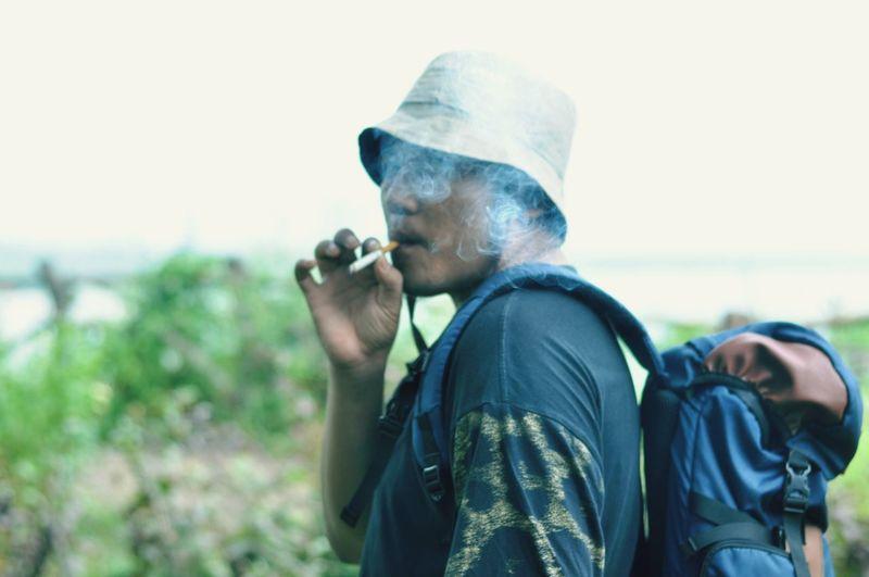 Man smoking cigarette against sky