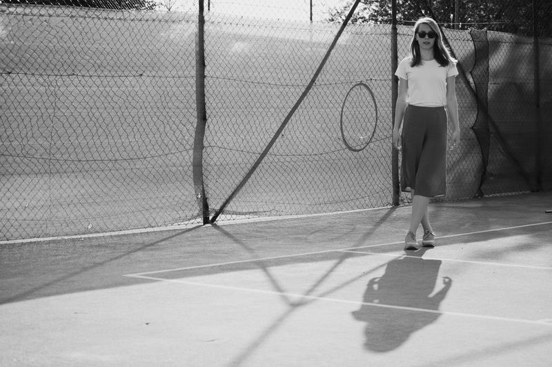 Full length portrait of woman standing on tennis court against fence