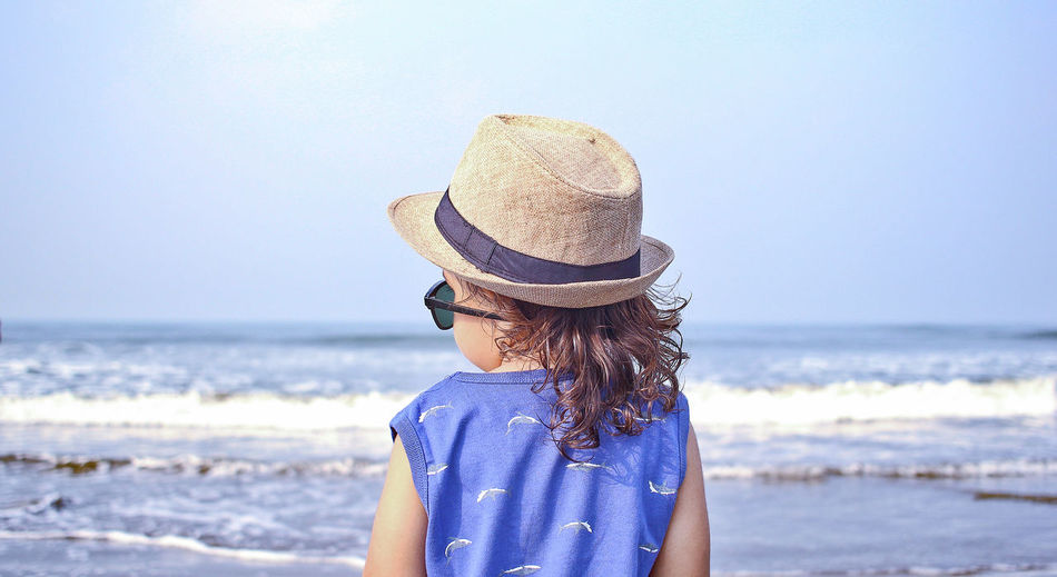 Boy Wearing Hat At Beach Against Clear Sky