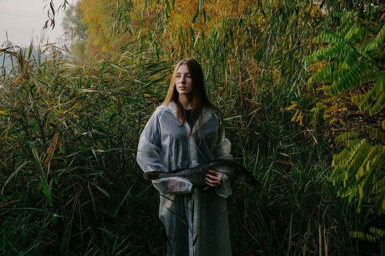 Real People Lifestyles Outdoors Nature Portrait Portrait Of A Woman Young Adult Front View Plant Young Women Beautiful Woman Fish Fishing Autumn colors Autumn Fall Plants Leisure Activity Green Color Nature Green Fisherman Raincoat Forest Contemplation