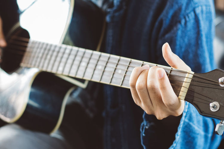 Midsection of man playing guitar at home
