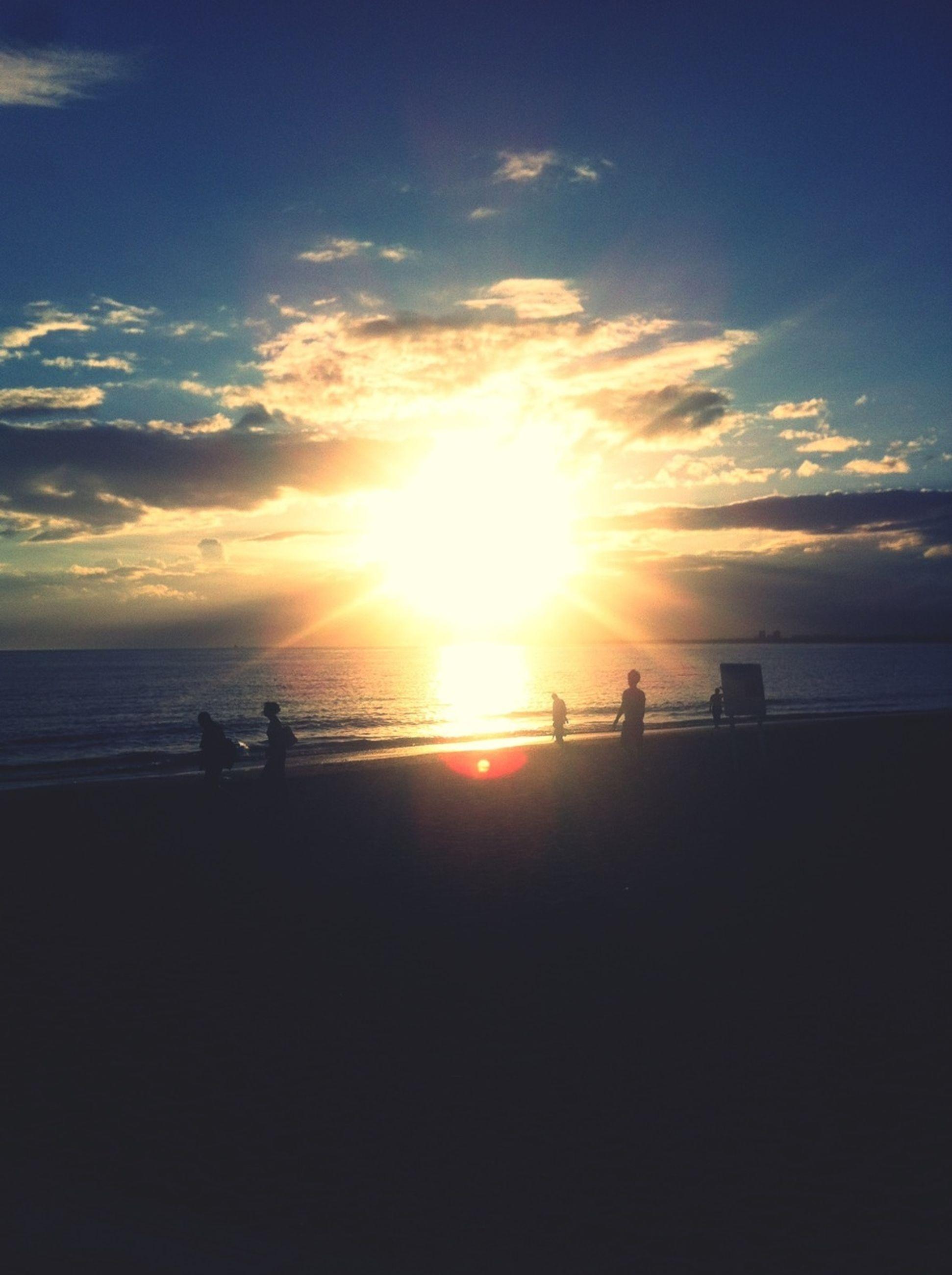 sea, sunset, horizon over water, silhouette, sun, water, beach, sky, scenics, beauty in nature, tranquil scene, tranquility, shore, sunlight, leisure activity, men, nature, lifestyles, idyllic