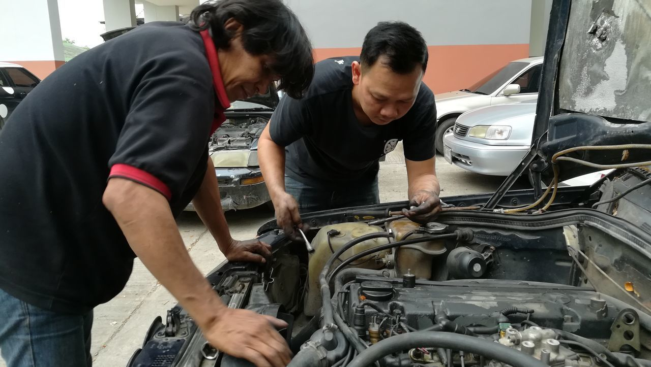 car, real people, two people, auto repair shop, mid adult men, mechanic, transportation, land vehicle, indoors, day, repairing, working, togetherness, occupation, young adult, people