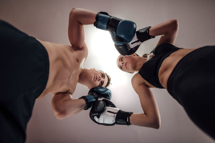 Portrait of man and woman kick boxers standing against each other with boxing gloves in ring. Low angle view of man and woman at kick boxing fighting position. Kickboxing Man Woman Couple Boxing Gloves Boxer Boxers Excercise Fitness Together Martial MuayThai Muay Thai Kick Gym Ring Match Punch Hit Hitting Sport Competition Fight Training