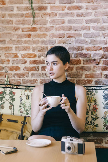 Woman with short hair holding coffee while sitting in cafe