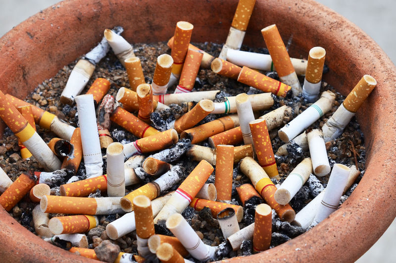 Close-Up Of Cigarette Butts In Container