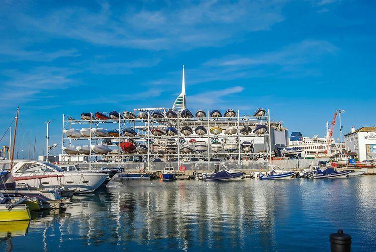 Boats Arranged In Racks At Harbor Against Blue Sky